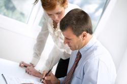 Dos trabajadores mirando una documentación (Fotolia). Oficina de atención a la discapacidad