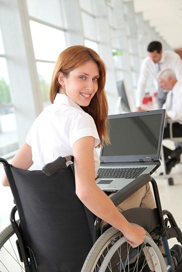 Qué es Discapnet, una joven en silla de ruedas en su oficina y con su ordenador en sus piernas