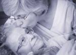 Cuidadora besando a mujer anciana en Respiro familiar