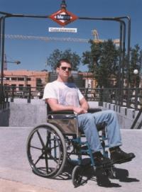 Joven en silla de ruedas delante de parada de metro para tomar un transporte público