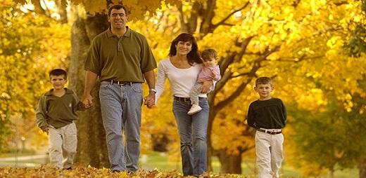 Tratamiento fiscal de la discapacidad, una familia con sus tres hijos paseando por un campo