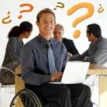 Joven en silla de ruedas con portatil y simbolos de interrogación de preguntas y respuestas