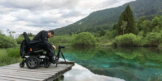 hombre en silla de ruedas haciendo fotos en pasarela de madera de un lago, para reconocimientos Destinos Turísticos Accesibles