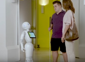 hombre con ceguera y acompañante junto a Paca, referente de robótica asistencial