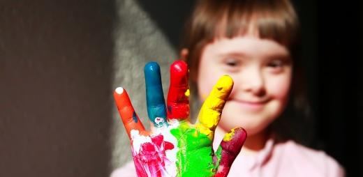 niña con síndrome de down con mano pintada de colores