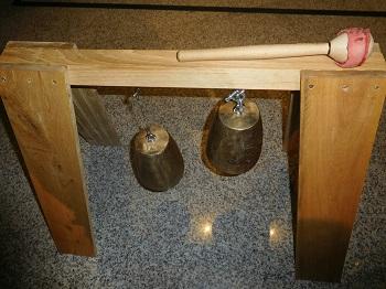 pieza de madera con campanas de cobre para tocar