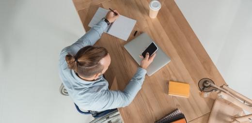 joven en silla de ruedas en su mesa de trabajo con móvil, portátil y cuadernos