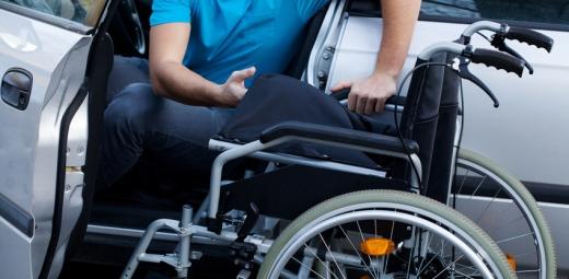 persona saliendo de su transporte privado, el coche, para pasar a la silla de ruedas