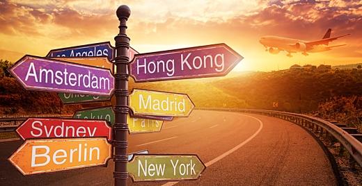 señales que indican destinos turísticos como Amsterdan, Madrid, etc y de fondo un avión y una carretera