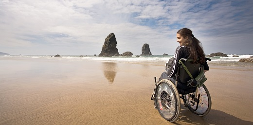 persona en silla de ruedas en la playa, pensando en la vuelta de vacaciones
